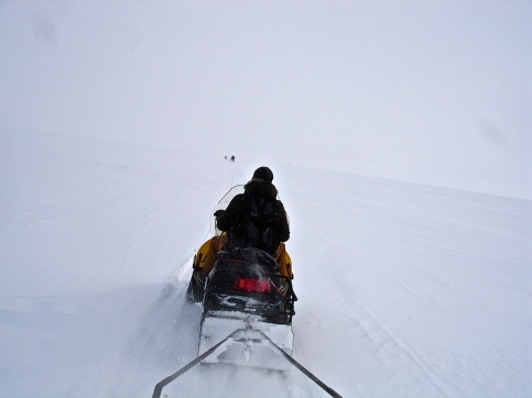 Riding a snowmobile to our sampling site on the frozen sea ice.